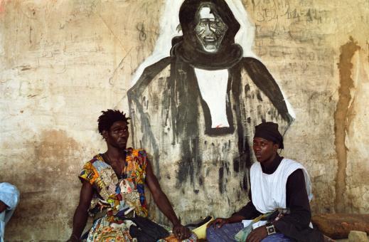 Ousmane pose avec un autre Baye Fall devant un mur décoré d'un grand portrait d'Ibrahima Fall. Touba, Sénégal, février 2008.