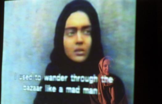 Niki Karimi derrière un écran sur lequel est projeté un de ses films. Téhéran, Iran, septembre 2006.
