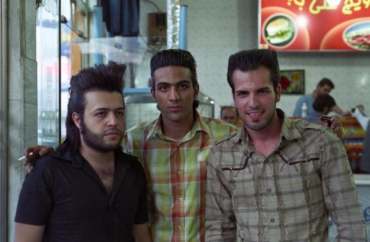 Trois amis en chemises fantaisie et coupes de cheveux étudiées posent dans un restaurant routier. Qom, Iran, octobre 2006.