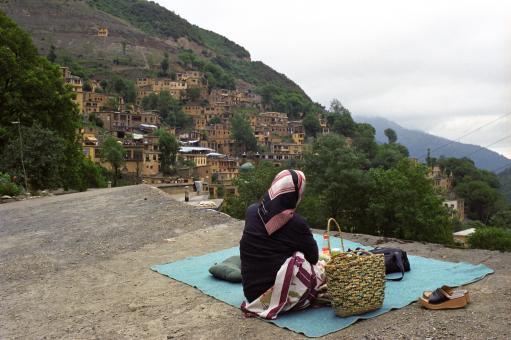 Une femme regarde le paysage depuis un toit-terrasse. Masuleh, Iran, août 2006.
