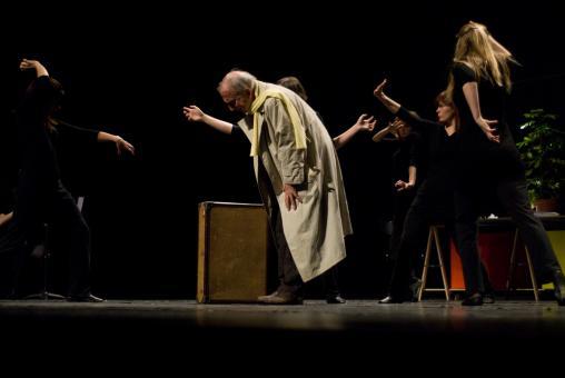 Deux bras d'une choreute dépassent derrière le père en imperméable, penché près de sa valise, autour duquel le chœur évolue d'une façon menaçante. Nanterre, octobre 2009.