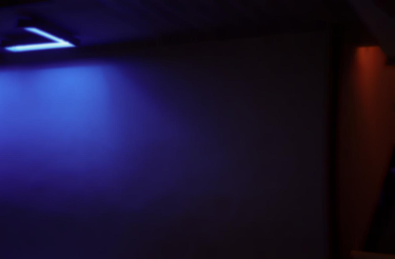 Mur éclairé par un néon bleu en forme de L, à droite un pan de mur perpendiculaire prend une lumière rouge. Paris, juillet 2006.