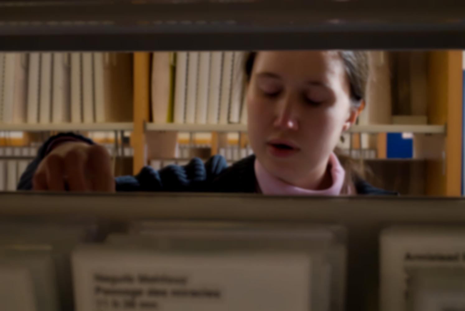 La nouvelle mediathèque de l'Association Valentin Haüy (AVH) : Céline range des livres parlés qui ont été rendus en lisant leurs étiquettes en braille. Paris, mars 2009.