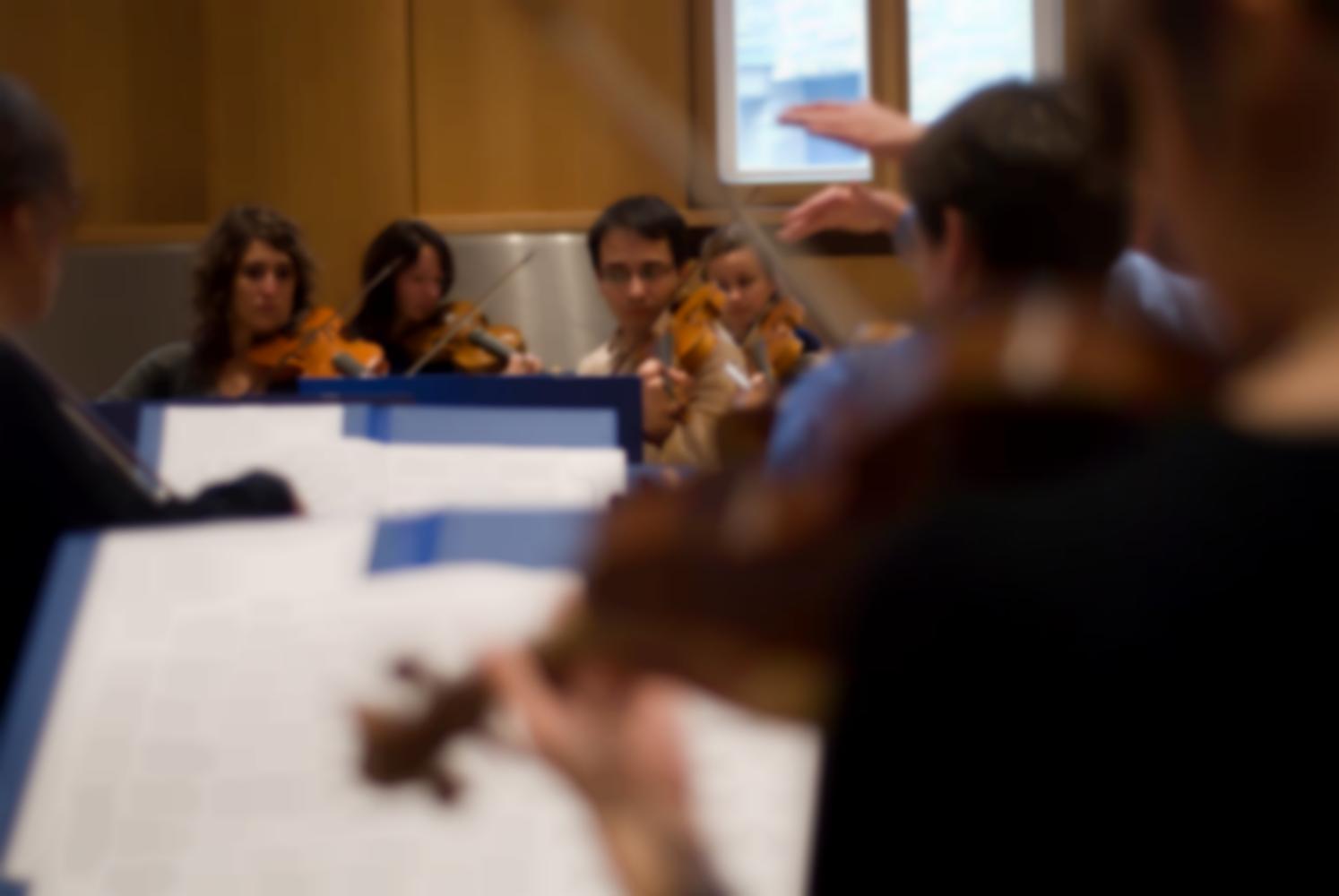 Les mains du chef d'orchestre apparaissent parmi les premiers violons, de dos au premier plan, et les seconds violons de face. Echternach, Luxembourg, octobre 2009.