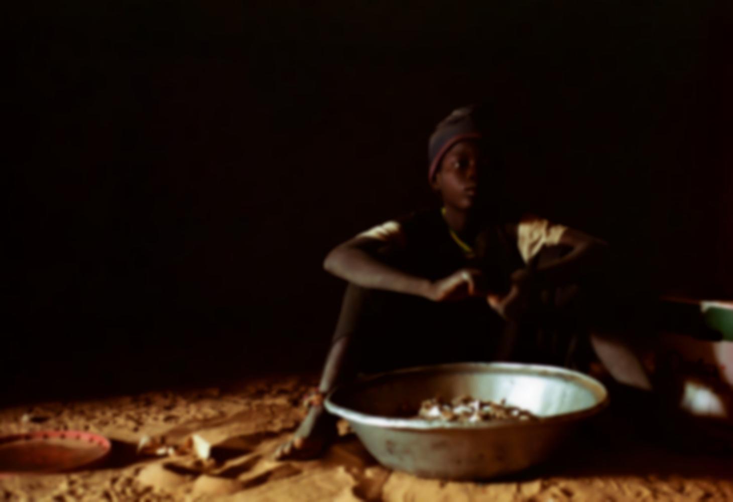 Assis sur le sol de sable, une grande bassine métallique devant lui, Aliou découpe du carton en petits morceaux. Touba, Sénégal, février 2008.