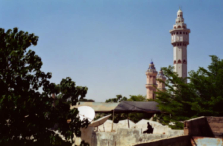 Derrière des arbres et des maisons, les minarets de la mosquée de Touba. Touba, Sénégal, février 2008.