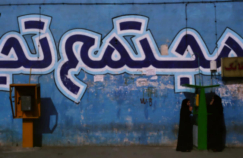 Deux femmes en tchadors téléphonent à une cabine publique verte, près d'une autre jaune, devant un mur bleu décoré de grandes inscriptions en persan. Shahr-e-Rey, Iran, mars 2007.