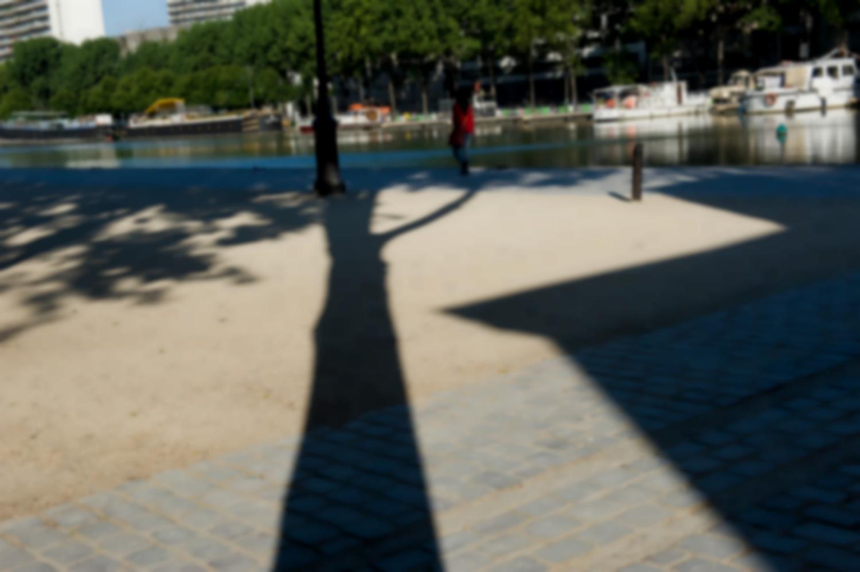 Le quai de la Loire, pavé puis sable, une passante, le bassin, des bateaux, les arbres du quai de Seine, et en travers, l'ombre allongée d'un arbre. Paris, mai 2011.