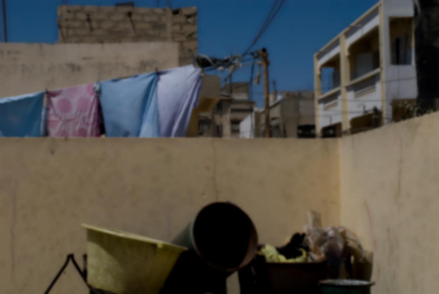 Devant le muret qui entoure le toit, des seaux et des bassines en plastique. Derrière, du linge qui sèche, des immeubles, peints ou non, et un enchevêtrement de fils électriques. Dakar, Sénégal, mars 2010.