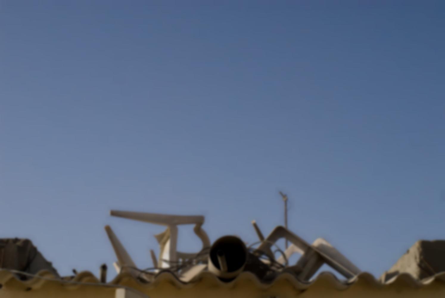 Des chaises en plastique blanc, un gros tuyau, un câble... sont empilés sur un toit de plastique ondulé, pris entre deux immeubles de parpaings. Dakar, Sénégal, mars 2010.