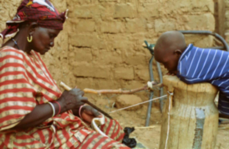 Rakia découpe une lanière de peau sous le regard attentif de son petit-fils appuyé sur un mortier renversé. Bosseye Dogabe, Burkina Faso, mai 2008.