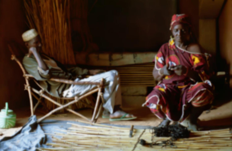 Rakia à l'ouvrage en compagnie de son ami Mohammed, assis dans un fauteuil de bois. Bosseye Dogabe, Burkina Faso, mai 2008.