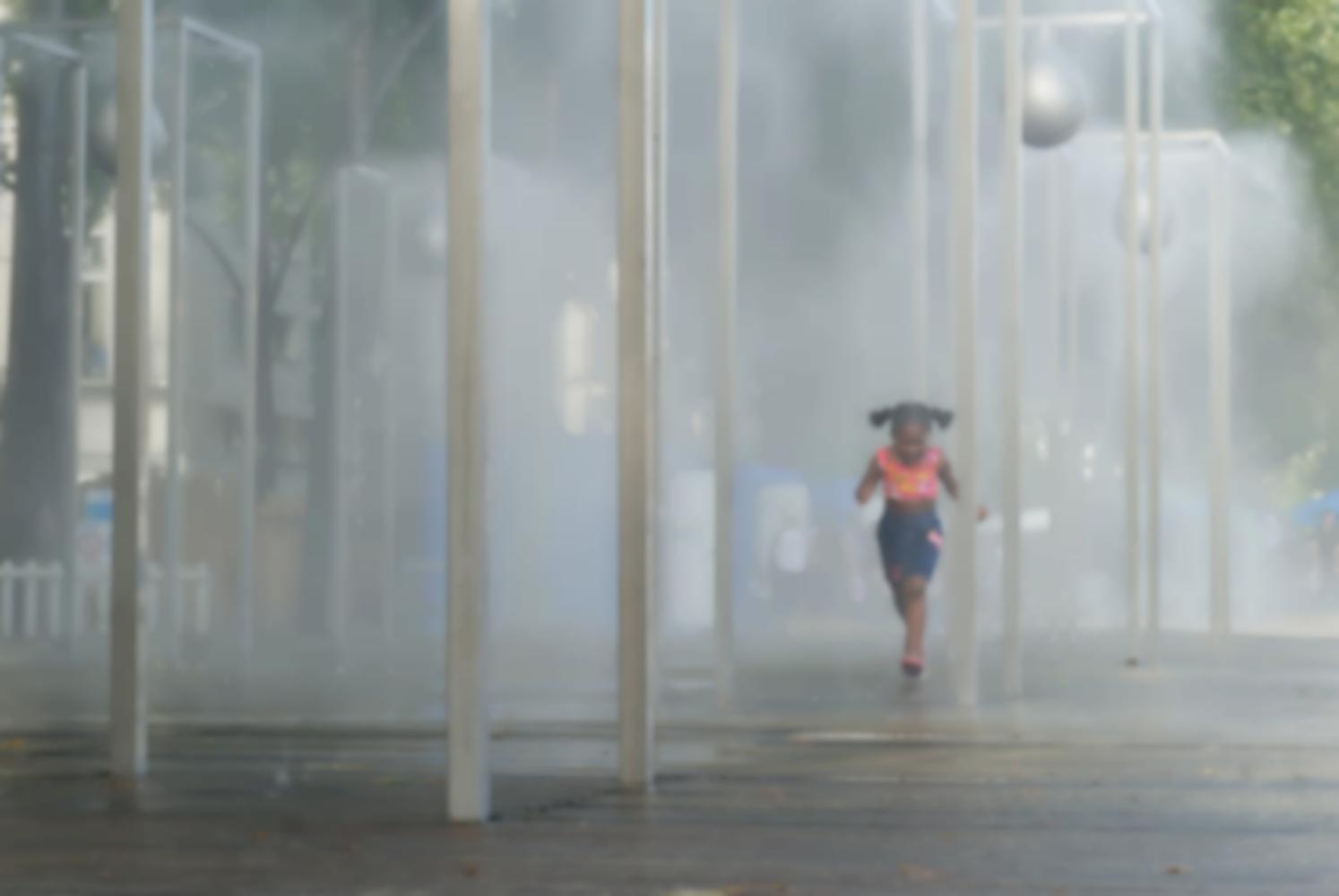 Une petite fille à couettes en débardeur rose court parmi les poteaux auxquels sont accrochés les brumisateurs. Paris, août 2010.