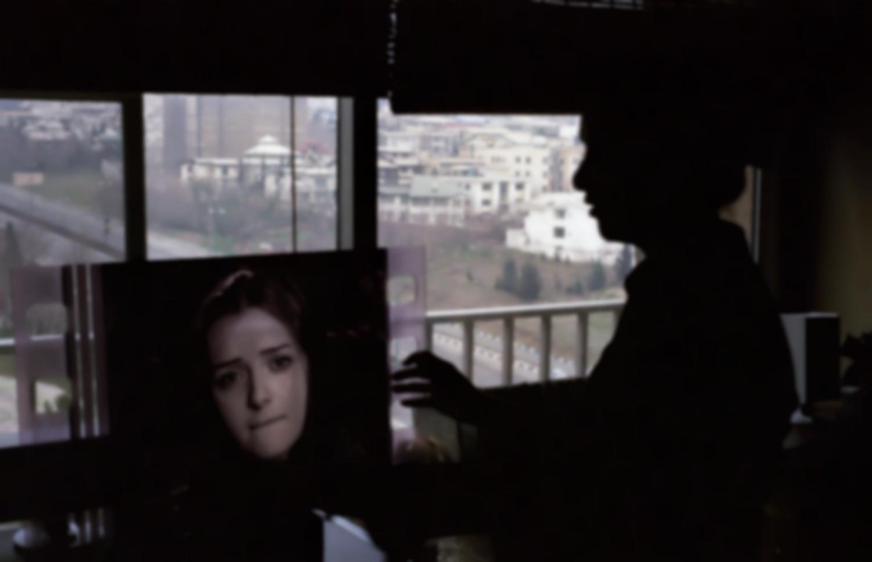La silhouette en contrejour de Taraneh Alidousti tient un photogramme la représentant dans un court-métrage d'Abbas Kiarostami. Téhéran, Iran, février 2007.