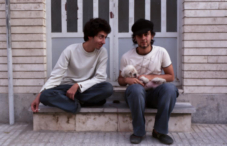Deux jeunes gens et un petit chien sur le perron d'un immeuble de quartier résidentiel. Téhéran, Iran, octobre 2006.