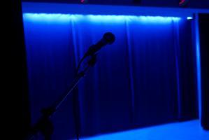 Un micro attend sur une scène vide éclairée à la lumière noire. Paris, novembre 2009.