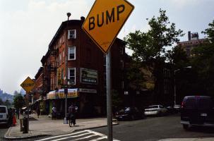 A l'entrée d'un passage piétons, près d'immeubles de briques, un panneau carré jaune : BUMP. New York, juin 2003.