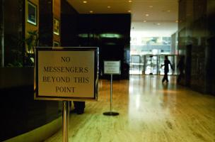 A l'entrée d'un hall d'immeuble dont on aperçoit une autre porte, un panneau interdit le passage : No messengers beyond this point. New York, juillet 2003.