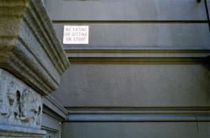 Sur la façade d'immeuble d'habitation, une petite plaque de cuivre : No eating or sitting on stoop. New York, juillet 2003.