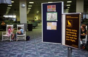 Dans un hall d'attente de l'aéroport de Newark, deux fillettes sont assises sur des rocking-chairs blancs, invitées par un panneau : Please enjoy our Rocking Chairs while you wait for your flight. New York, août 2003.