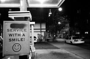 A l'entrée d'une station-service à Manhattan, sur fond d'Empire State Building, un panneau Service with a smile ! :) accueille les clients. New York, juin 2003.