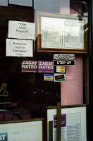Sur la porte vitrée d'un restaurant, en plus des informations habituelles, quelques injonctions : Proper Attire Required, Restrooms Are For Customers Only (deux fois) et Step up. New York, juin 2003.