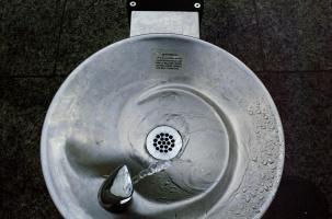 Collée sur une fontaine publique, une étiquette décrit son fonctionnement : Attention. This is a freeze-proof drinking fountain and has a delayed water action. Press handle and wait. Thank you. New York, juin 2003.