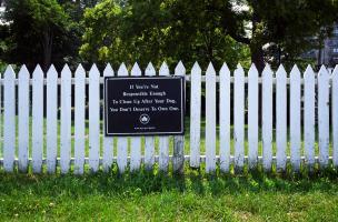 Dans un parc de Staten Island, une barrière de planches peintes en blanc plantée dans le gazon porte un panneau : If You're Not Responsible Enough To Clean Up After Your Dog, You don't Deserve To Own One. New York, juillet 2003.