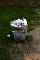Dans un parc, un seau en zinc cabossé utilisé comme poubelle essaie de se défendre : Hot ashes only. New York, juin 2003.