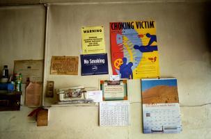 Sur le mur d'un restaurant, parmi divers objets, des avertissements sur les dangers de l'alcool pendant la grossesse, une interdiction de fumer, des instructions de réanimation et des informations sur l'inspection sanitaire. New York, juillet 2003.