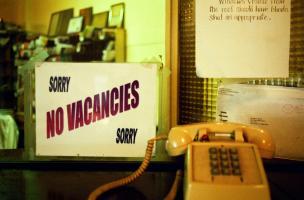 A l'accueil d'un hôtel, derrière un vieux téléphone, une annonce : Sorry, No vacancies, Sorry et une notice pour les clients : Windows visible from the roof should have blinds shut as appropriate. New York, juillet 2003.