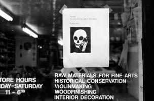 Collée sur la porte vitrée d'un magasin, au-dessus des horaires et d'une liste de produits, une prière illustrée d'un dessin de squelette en train de téléphoner : Please, No cell phone calls in the store. Thank you. New York, juin 2003.