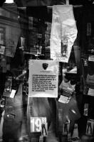 Dans la vitrine d'une boutique de jeans: ATTENTION. Avoid embarrassment for yourself and this store. Shoplifting is a crime and will be prosecuted to the fullest extent of the law. The police will be called and you will be arrested. New York, juin 2003.