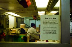 Avis de recherche sur la vitre d'un bureau ou d'une loge de concierge : une récompense est proposée par les Crime Stoppers en échange d'informations sur un meurtre. New York, juin 2003.