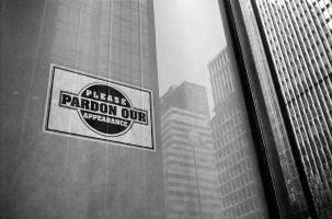 La façade vitrée d'un gratte-ciel, dans laquelle se reflètent les immeubles voisins, et des excuses faisant allusion à des travaux en cours : Please pardon our appearance. New York, juin 2003.