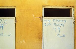 Dans un mur jaune, deux portes blanches avec inscriptions en plusieurs langues et alphabets - dont WC et Wishing room. Teseney, Erythrée, février 2005.