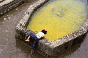 Une petite fille se penche sur un bassin au fond jaune. Masuleh, Iran, août 2006.