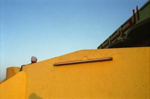 Une tête enturbannée dépasse du mur jaune de la terrasse d'un restaurant routier. Egypte, avril 2004.