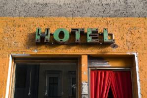 Façade jaune et grise, ornée d'une vieille enseigne Hotel verte et rouille, et de rideaux rouges à sa porte. Berlin, septembre 2009.