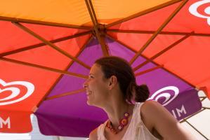 Solveig souriante sous un parasol mauve, rouge et orange. Arradon, août 2009.