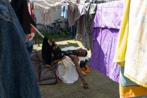 Thioub se réveille sur un lit de camp installé au milieu du linge multicolore mis à sécher dans la cour du foyer Rochebrune. Montreuil, juin 2009.