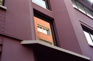 Façade d'un immeuble mauve, et dans une de ses fenêtres, reflet d'un autre en briques. Paris, printemps 2006.