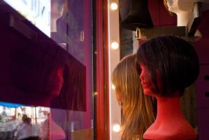 Présentoirs de perruques dans la vitrine d'un coiffeur. Vierzon, août 2009.