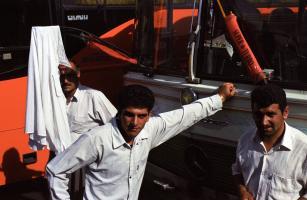A la gare routière, trois hommes parmi les bus, une chemise blanche accrochée à un essuie-glace. Téhéran, Iran, juillet 2006.
