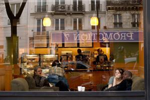 Derrière la vitrine d'un café des grands boulevards, des clients regardent passer une manifestation. Paris, janvier 2009.