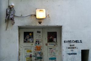 A côté d'une double porte couverte d'affiches et d'autocollants déchirés, surmontée d'une lumière et d'une sorte de grande marionnette, un graffiti au pochoir cite Barschels. Berlin, septembre 2009.