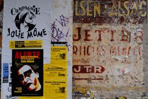 Affiches de la compagnie Jolie Môme et d'une réunion politique sur le Vénézuela, collées sur un mur peint d'une ancienne enseigne cour des Petites Ecuries. Paris, janvier 2009,.