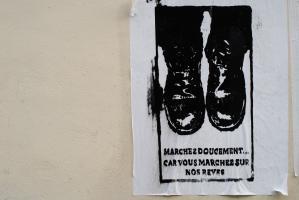 Graffiti au pochoir réalisé sur une affiche blanche, représentant des pieds chaussés de godillots au-dessus de quelques lignes. Paris, avril 2009.