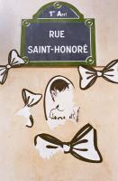 Sur un mur rosâtre, une plaque de la rue Saint-Honoré a été décorée de nœuds dessinés sur du papier blanc et découpés, et d'un autre dessin style manga qui a été déchiré. Paris, septembre 2008.