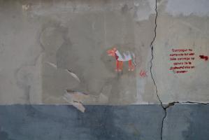 Collage déchiré représentant un animal orange, silhouette d'un autre collage, et de l'autre côté d'une lézarde, une phrase au pochoir. Paris, mai 2010.